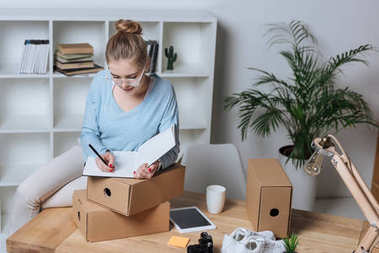 portrait of concentrated entrepreneur making notes in notebook while working at home office