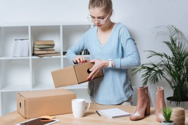 online shop proprietor with cardboard boxes working at home office