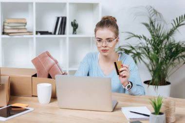 portrait of focused woman with credit card in hand looking at laptop screen at table