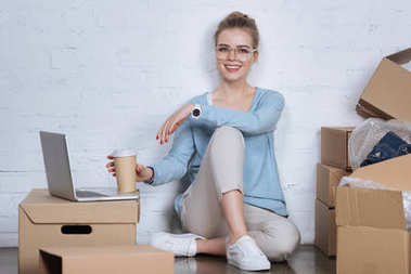 smiling entrepreneur with coffee to go sitting on floor at home office