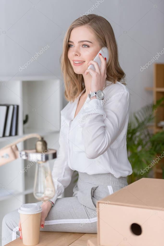 portrait of smiling businesswoman with coffee to go talking on smartphone