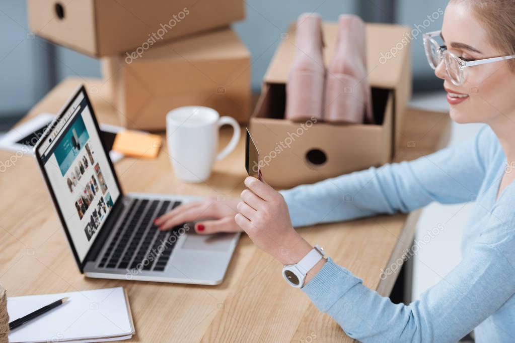 selective focus of woman with credit card in hand looking at laptop screen at table