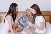 Fényképek többnemzetiségű lányok ágyon ül, és beszél a divatlapok
