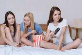 Fényképek multikulturális lányok ülnek szoba-és pattogatott kukorica és tv-nézés