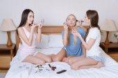 többnemzetiségű lányok ágyon ül, és ennek smink