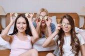 Fotografie drei schöne multiethnischen Mädchen für Augen mit Gurke Stücke