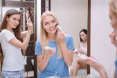 Fotografie attractive girl applying foundation powder with makeup brush in bathroom with friends