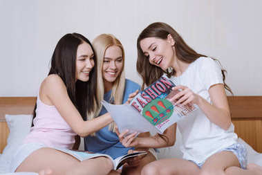 smiling multiethnic friends sitting on bed and reading fashion magazines
