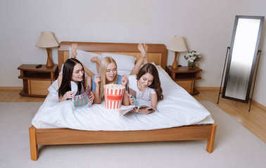happy multiethnic girls lying on bed with popcorn and reading magazines