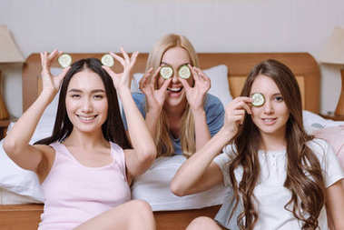 three beautiful multiethnic girls covering eyes with cucumber pieces