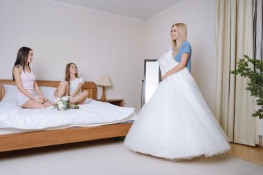 girl preparing for wedding and showing multicultural friends wedding dress