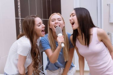 multiethnic friends singing in bathroom with round comb