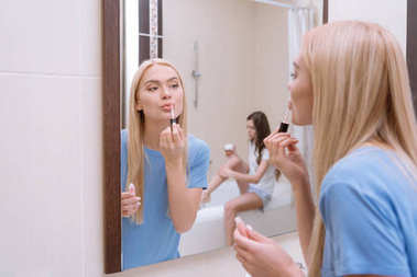Attractive girl applying lips gloss in bathroom stock vector