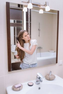 attractive girl combing hair in bathroom in the morning