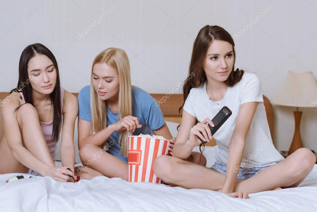 multicultural girls sitting on bed with popcorn and watching tv