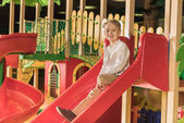 Fotografie Netter kleiner Junge lächelt in die Kamera, während er auf der Rutsche im Indoor-Spielcenter spielt