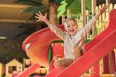 glücklicher kleiner Junge lächelt in die Kamera, während er auf der Rutsche im Unterhaltungszentrum spielt