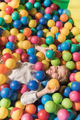 Fotografie vysoký úhel pohled milý chlapeček se usmívá na kameru při ležení v bazénu s barevnými míčky