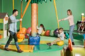 Fotografie Lächelnde Eltern mit Blick auf glückliche Kinder, die auf Schaukeln im Indoor-Spielcenter schaukeln