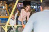 Selektivní fokus rodičů s happy malá dcerka hrát hokej v herním centru