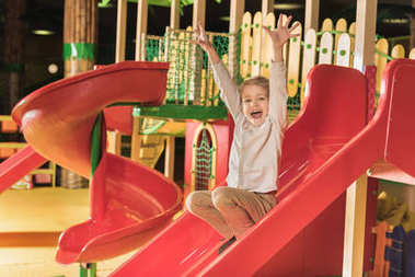 adorable happy little boy with raised hands playing on slide in game center