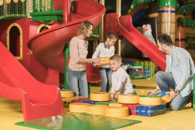 happy family with two little children playing together in game center