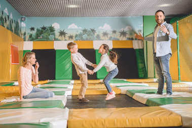 happy parents with adorable little kids holding hands and jumping in entertainment center