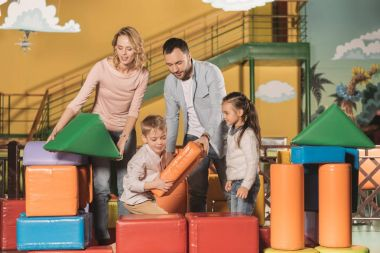 happy family playing together with colorful blocks at indoor play center