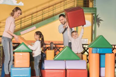 happy family with two children building castle with colorful blocks at game center
