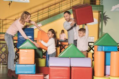 happy family building castle with colorful blocks at entertainment center