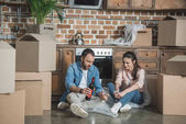 Photo young couple with bottle of wine celebrating relocation in new apartment