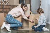 Fényképek boldog anya és fia támaszkodva karton doboz, miközben az otthon