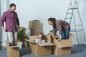 Photo happy parents looking at son sitting in cardboard box during relocation