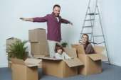 Photo happy family having fun with cardboard boxes while moving home