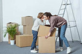 Photo little boy whispering something to mother while packing cardboard boxes together
