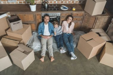 high angle view of happy family smiling at camera while sitting on floor during relocation