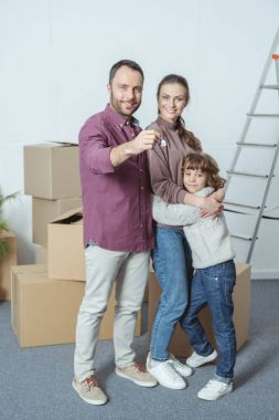 happy family with one kid smiling at camera and holding key from new apartment