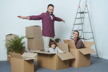happy family having fun with cardboard boxes while moving home