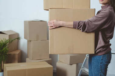 cropped shot of woman holding cardboard boxes while moving home
