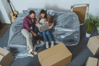 high angle view of family with one child using laptop while moving in new home
