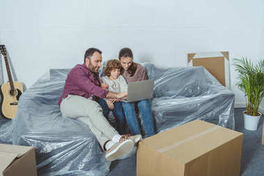 family with one kid using laptop while moving in new apartment