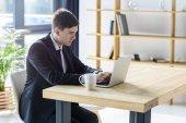 Mladý podnikatel, pracovat na notebooku v moderní kanceláři