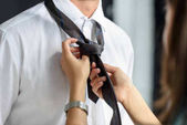 Photo Woman ties a knot on male tie