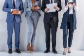 Fotografie Gruppe erfolgreicher Geschäftsleute in Anzügen, die an der Wand stehen