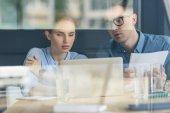Za skla pohled pozorný podnikatel a podnikatelka se o projektu v moderní kanceláři