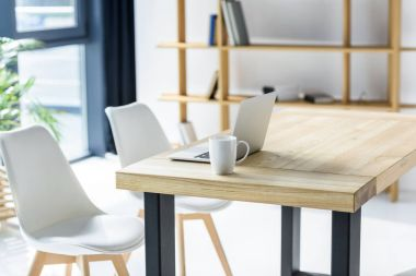 Laptop and coffe cup on table in modern office