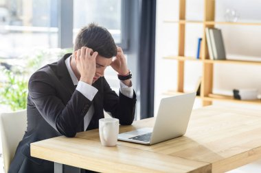 Young businessman suffers from headache while working on laptop