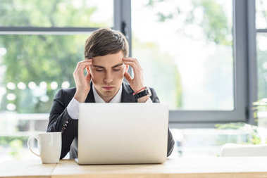 Businessman suffers from headache while working on laptop