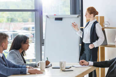 Confident businesswoman presenting her idea by flip chart to colleagues in modern office