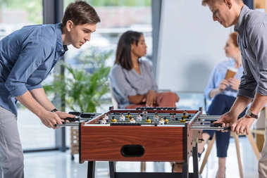 Two businessmen playing table football while young businesswomen chatting during break in modern office